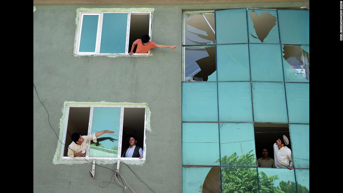 "Residents look at a building's broken windows after <a href=""http://www.cnn.com/2016/09/06/asia/care-kabul-ngo-attack/"" target=""_blank"">a car bomb blast</a> near the compound of the nongovernmental organizational CARE in Kabul, Afghanistan, on Tuesday, September 6."