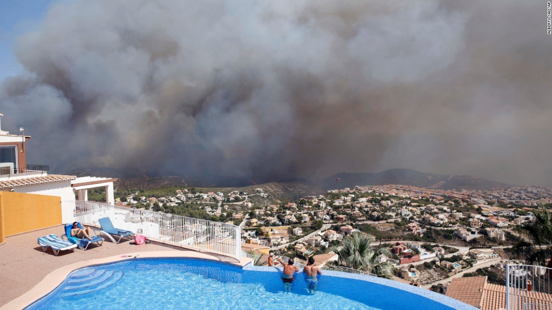 "Two men watch a wildfire from afar as it burns in Benitachell, Spain, on Monday, September 5. <a href=""https://www.theguardian.com/world/2016/sep/05/wildfire-near-spanish-resort-javea-evacuations"" target=""_blank"">According to the Guardian</a>, authorities said more than 200 firefighters were working to combat the forest blaze near Valencia, and more than 1,000 residents and tourists were forced to flee."