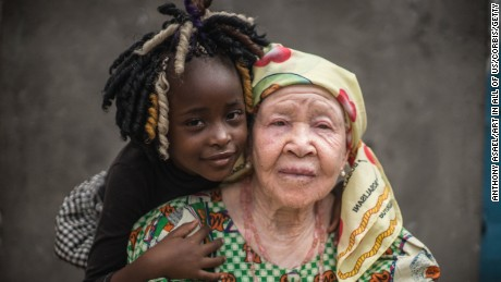 Democratic Republic of Congo (DRC), Kinshasa, Albino grand-mother (Marie Margherite Embongo Hoheka & Dorianne) posing against a grey wall with her black grand-daughter, Kinshasa, (MR)