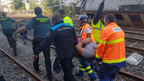 Rescuers carry an injured passenger away from the wreckage.