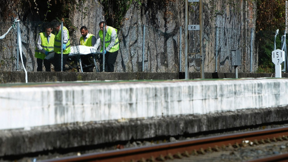 A body is transported from the crash scene. The train's Portuguese driver was among the dead.