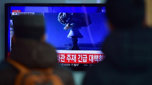 """TOPSHOT - ADDITION- People watch a news report on North Korea's first hydrogen bomb test at a railroad station in Seoul on January 6, 2016. South Korea """"strongly"""" condemned North Korea's shock hydrogen bomb test and vowed to take """"all necessary measures"""" to penalise its nuclear-armed neighbour.  The image shown on TV shows files images from other nuclear tests from other countries and the caption in red at the bottom of the screen reads """"the Blue House will convene an emergency meeting of the NSC, the National Security Council.""""   AFP PHOTO / JUNG YEON-JE / AFP / JUNG YEON-JE        (Photo credit should read JUNG YEON-JE/AFP/Getty Images)"""