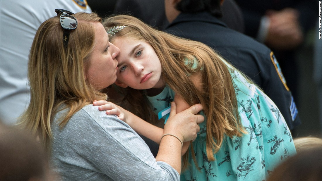 Family members embrace Sunday during the 15th-anniversary service at the 9/11 Memorial and Museum.