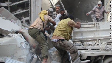 EDITORS NOTE: Graphic content / Syrian men evacuate a victim from the rubble of a building following a reported  air strike on the rebel-held northwestern city of Idlib on September 10, 2016.  More than 290,000 people have been killed in Syria since its conflict erupted in March 2011, and millions displaced by the fighting. / AFP / Omar haj kadour        (Photo credit should read OMAR HAJ KADOUR/AFP/Getty Images)
