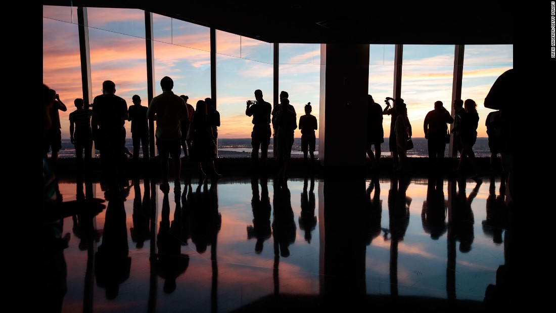 Visitors view the sunset from the observatory of One World Trade Center on Sunday, September 11, the 15th anniversary of the 2001 attacks.
