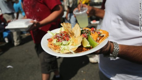 A man carries a plate of tacos on July 20, 2014 in Valhalla, New York.