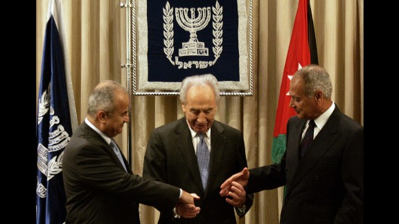 Israeli President Shimon Peres, center, joins hands with Jordan