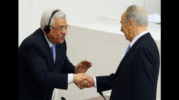 Palestinian Authority President Mahmoud Abbas, left, congratulates President Shimon Peres of Israel after Peres addressed Turkey