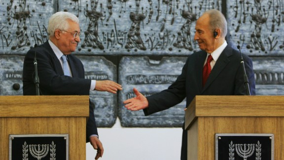 Palestinian President Mahmoud Abbas reaches to shake hands with Israeli President Shimon Peres prior to their meeting in Jerusalem on July 22, 2008. Abbas had threatened to withdraw his forces from West Bank cities unless Israel