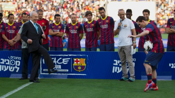 Israeli President Shimon Peres kicks the ball to FC Barcelona
