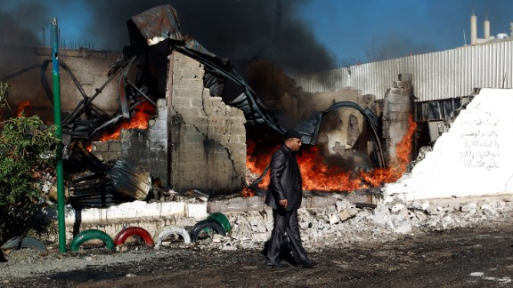 A man walks past a building hit by a Saudi-led coalition airstrike in February 2016, in the Yemeni capital, Sanaa.