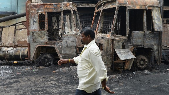 A pedestrian walks past the skeletal remains of a Karnataka state transport bus, September 13, following the clashes during the Cauvery water dispute in Bangalore.