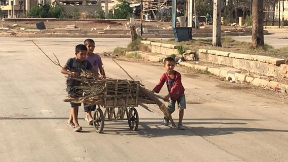 Children pushing cart loaded with firewood they collected in the Shihan neighborhood.