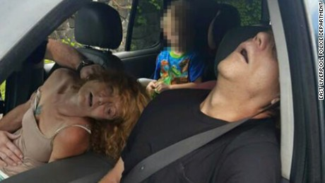 A woman and man in East Liverpool, Ohio, are seen passed out from a drug overdose as a child sits in the back seat of a car on Wednesday, September 7.