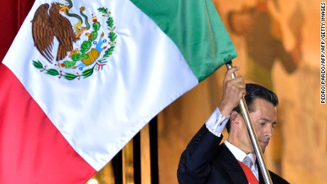 President Enrique Pena Nieto waves the Mexican National Flag.