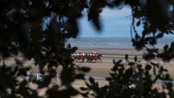 A view of the action as riders and jockeys come into view through a gap in trees above the beach.
