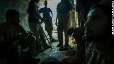Libyan forces take shelter in a derelict district close to the front line.