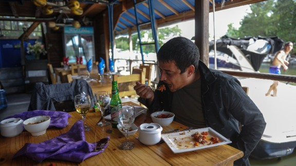 A man eats in a private restaurant in Havana where the lionfish is served.  There are increasing efforts to reduce the lionfish population by marketing them as food, with conservation group REEF producing a dedicated cookbook.