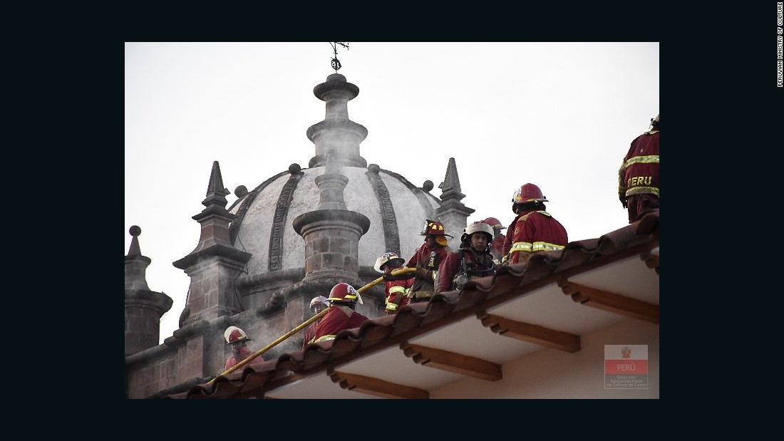 Firefighters check out damage to the roof of San Sebastian Church. The church's roof is in danger of collapsing.