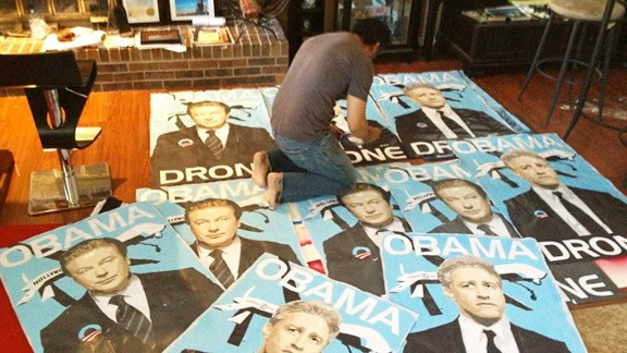 """Posters of actor Alec Baldwin and comedian Jon Stewart as """"Obama drones."""""""