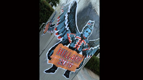 """A flying monkey, inspired by the ones that work for the Wicked Witch in """"The Wizard of Oz,"""" holds a """"Hillary 2016"""" sign."""