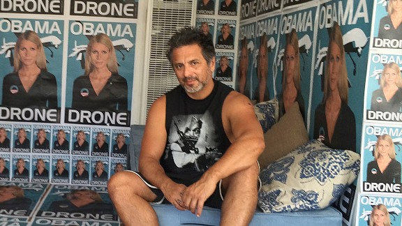 """The street artist Sabo rose to the national stage with art that often shocks, offends and confronts some of America's most controversial hot-button issues. Here, he poses in front of posters of actress Gwyneth Paltrow represented as an """"Obama drone."""""""