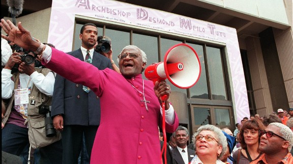 """Tutu joyfully shouts """"I am free! We are all free!"""" outside the Civic Centre in Cape Town in 1998. It was before a ceremony where he received the Freedom of the City award. In 1998, Tutu retired as the archbishop of Cape Town and became archbishop emeritus."""