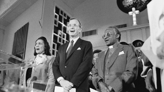 """Coretta Scott King, US Vice President George H.W. Bush and Tutu sing the civil rights hymn """"We Shall Overcome"""" during a service honoring Martin Luther King Jr. in January 1986."""