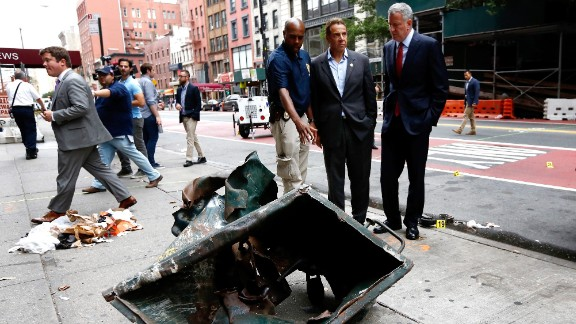 New York Mayor Bill de Blasio, right, and New York Gov. Andrew Cuomo, second right, look over the mangled remains of a dumpster Sunday, September 18, in New York
