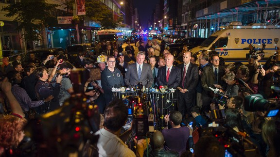 De Blasio, in the blue tie, speaks at a news conference near the scene on Saturday. He was joined by New York Police Commissioner James O