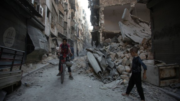 TOPSHOT - Syrians walk through the rubble following an airstrike on the regime-controlled neighbourdhood of Karm al-Jabal on September 18, 2016.   Syria's ceasefire was on the brink of collapsing Sunday, after a US-led coalition strike killed dozens of regime soldiers and Aleppo city was hit by its first raids in nearly a week.    / AFP / KARAM AL-MASRI        (Photo credit should read KARAM AL-MASRI/AFP/Getty Images)