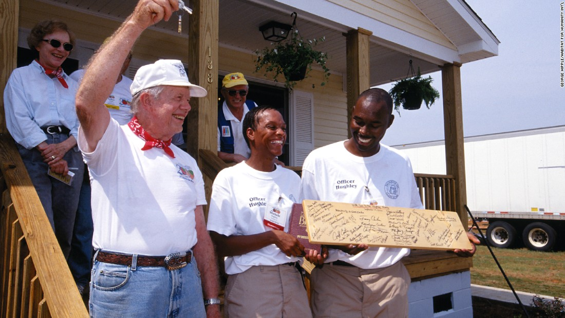 President Jimmy Carter presents Neal and Michele Hughley with the keys to their new Habitat house completed during the Jimmy Carter Work Project in 2000.