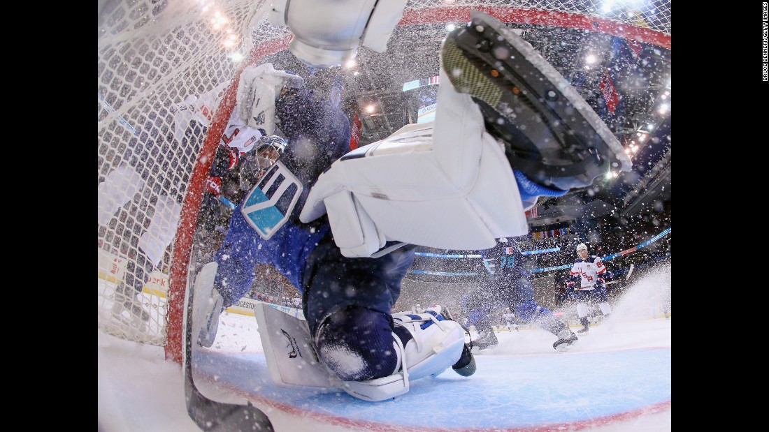 Team Europe goalie Jaroslav Halak is bumped by a member of Team USA during their World Cup opener on Saturday, September 17. Halak shut out the Americans 3-0.