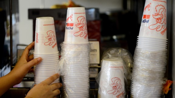 An employee of a fast food store arranges prohibited plastic cups at the Manila's financial district, Makati City on June 20, 2013. The Philippines' financial centre banned disposable plastic shopping bags and styrofoam food containers on June 20, as part of escalating efforts across the nation's capital to curb rubbish that exacerbates deadly flooding. AFP PHOTO/NOEL CELIS        (Photo credit should read NOEL CELIS/AFP/Getty Images)