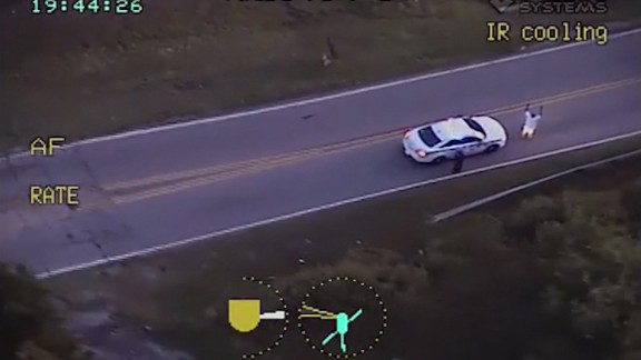 Video from a police helicopter circling above shows Terence Crutcher with his hands up as an officer approaches him.