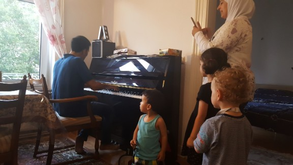 Aeham plays for his neighbours and kids at his new home in Wiesbaden, Germany.