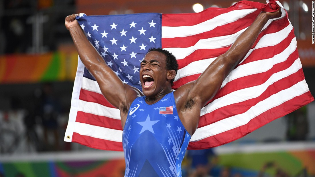 Olympic wrestler J'den Cox celebrates with the American flag after winning the bronze-medal match in his weight class.
