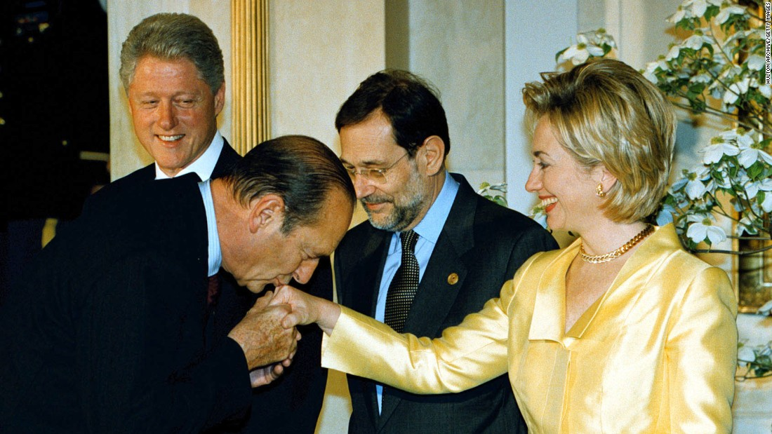 Chirac kisses the hand of U.S. first lady Hillary Clinton at a NATO summit in Washington in 1999.