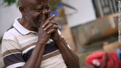 A man cries on September 20, 2016 near the offices of the main opposition Union for Democracy and Social Progress (UDPS) party which were torched overnight and early on September 20, in Kinshasa.