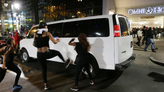 Protesters rushed police in riot gear at a downtown Charlotte hotel. Officers fired tear gas to disperse the crowd.