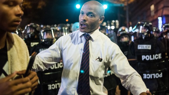 "Charlotte public defender Toussaint Romain pushes a protester back from a line of police. ""We can't lose any more lives, man. I'm a public defender. I can't represent any more people,"" he told CNN's Boris Sanchez."