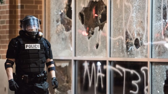 A police officer in riot gear stands near a damaged storefront on September 21.
