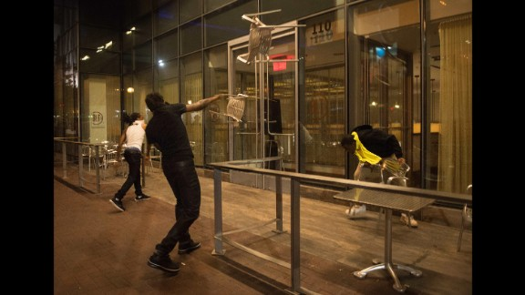 Protesters throw chairs at a restaurant.