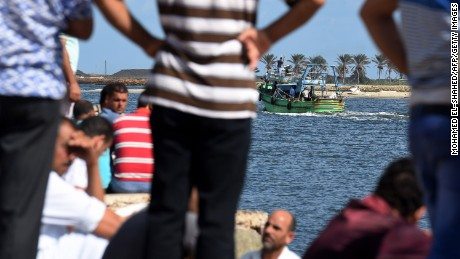 Egyptian men sit along the shore in the Egyptian port city of Rosetta on September 22, 2016 as they watch a boat departing for a search operation. A boat carrying up to 450 migrants capsized in the Mediterranean off Egypt's north coast, drowning 42 people and prompting a search operation that rescued 163 passengers, officials said. The vessel overturned off the port city of Rosetta, police and health officials said.