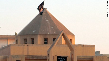 "The flag of the Islamic State of Iraq and the Levant (ISIL) flutters on the ""dome"" of the  Armenian Catholic Church of the Martyrs in the northern rebel-held Syrian city of Raqqa on September 28, 2013."