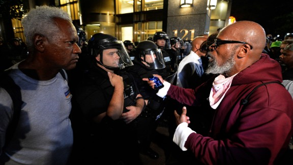 A protester, right, expresses his opinion to a police officer and another pedestrian near Trade and Tryon Streets in Charlotte on Thursday, September 22.