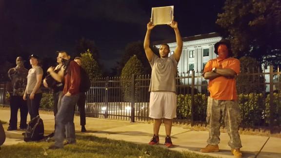 Alex Orange, 26, points a mirror at police Thursday.
