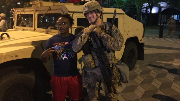 A protester joins a National Guardsman in Charlotte.