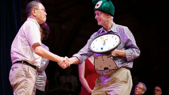 Atsuki Higashiyama, left, from Ritsumeikan University in Japan, accepts the Ig Nobel Perception prize for investigating whether things look different when you bend over and view them between your legs.
