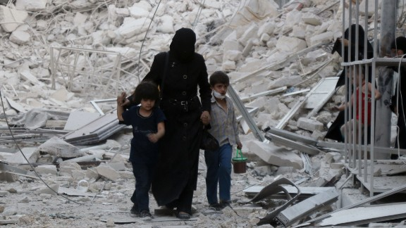 A Syrian family leaves the area following a reported airstrike on Friday, September 23, in rebel-held east Aleppo. Following the airstrike, recovery teams from Syria Civil Defense, known as the White Helmets, began working to free the trapped and recover the dead, including small children.